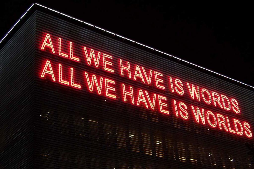 """Foto mit großem Neon-Schriftzug und den Sätzen """"ALL WE HAVE IS WORKDS"""" und """"ALL WE HABE IS WORLDS"""""""
